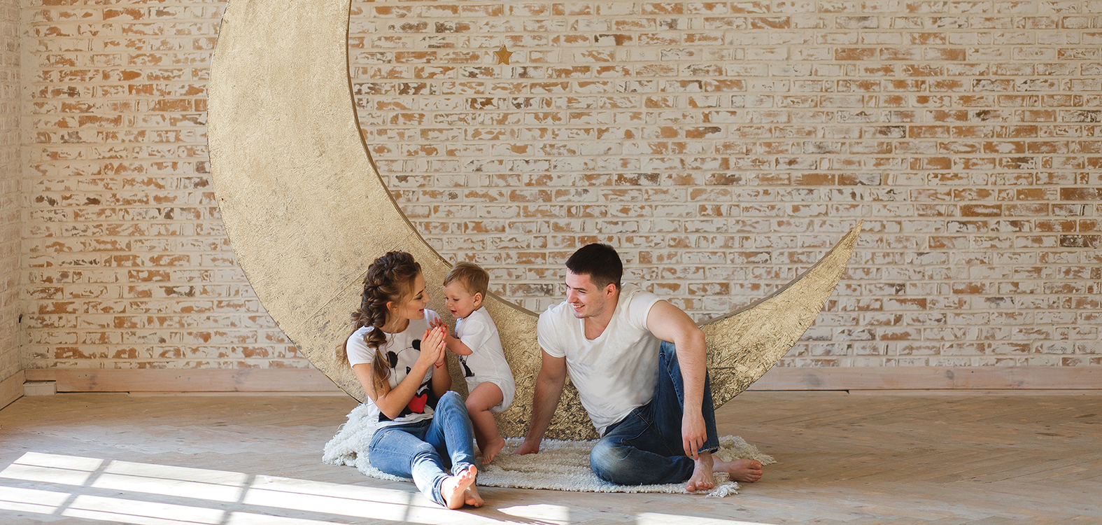 Happy family father, mother and child son near a blank brick wall in the room. Big moon on background.